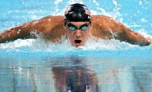 Phelps swimming in the water; he has a swim cap and goggles and the top of his torso and arms and head are out of the water as he takes a breath