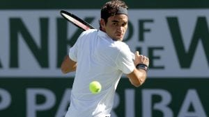 image of Federer wearing a white tennis shirt and black sweatband holding a tennis racket looking at a ball as it is coming towards him, about to swing his racket to hit it