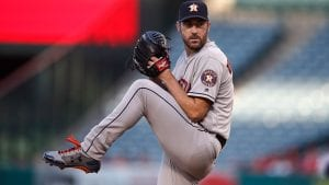 Verlander about the pitch a baseball; he has his hands in his glove with the ball, his leg is raised and he is looking in the distance