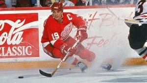 Yzerman skating wearing a Red Wings jersey, he is holding his stick out in front of him going forward a puck