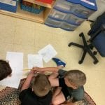 three students working on drawing their drafts of the wind turbines