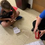 two boys work on a mock up of a wind turbine
