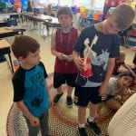 three students show off their wind turbine working