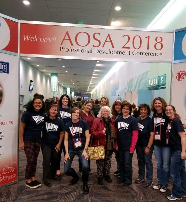 Detroit Orff Schulwerk Members pose for a photo under the AOSA 2018 National Conference Banner.