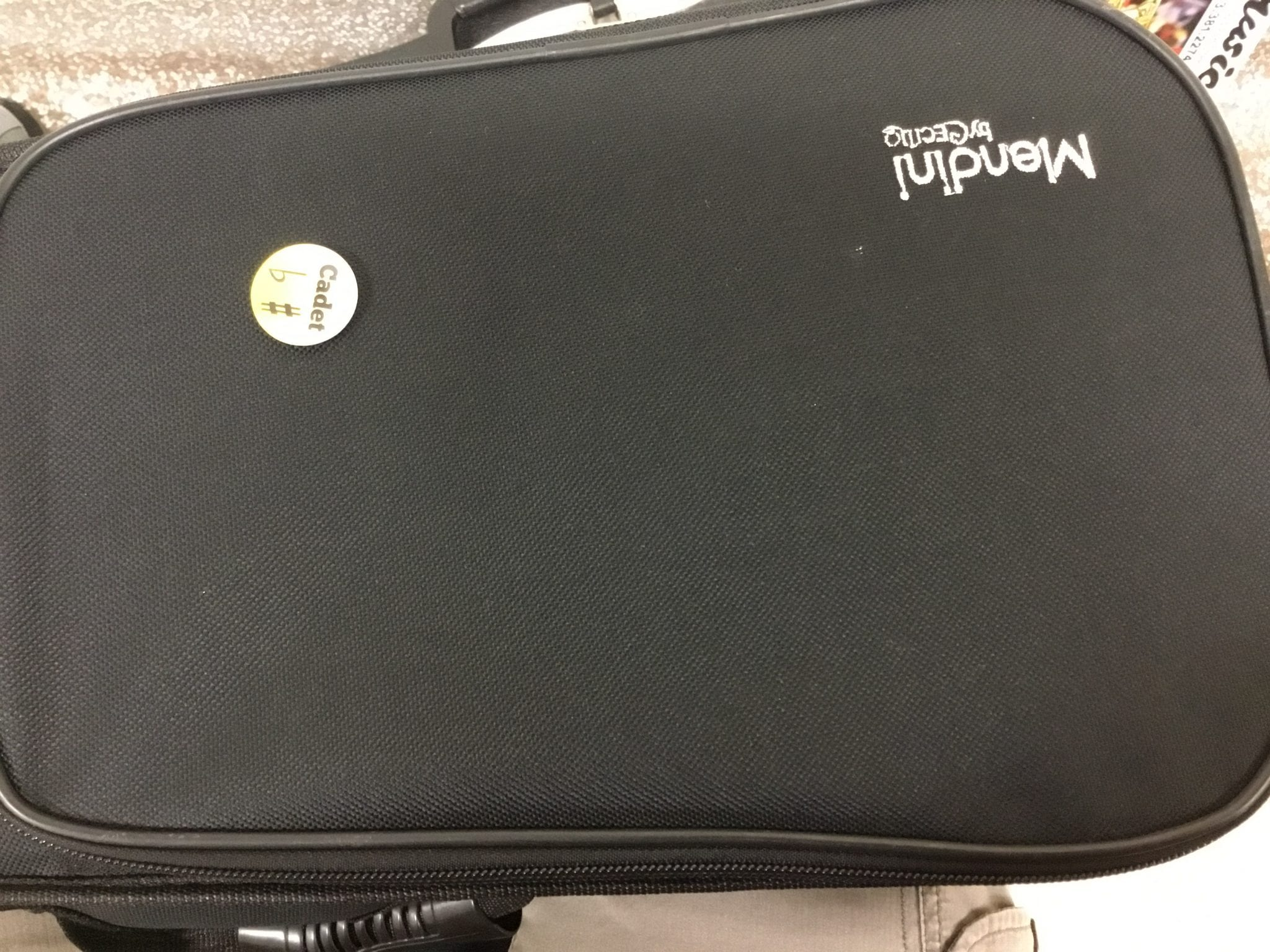 A proud student displays the earned cadet pin on his or her instrument case.