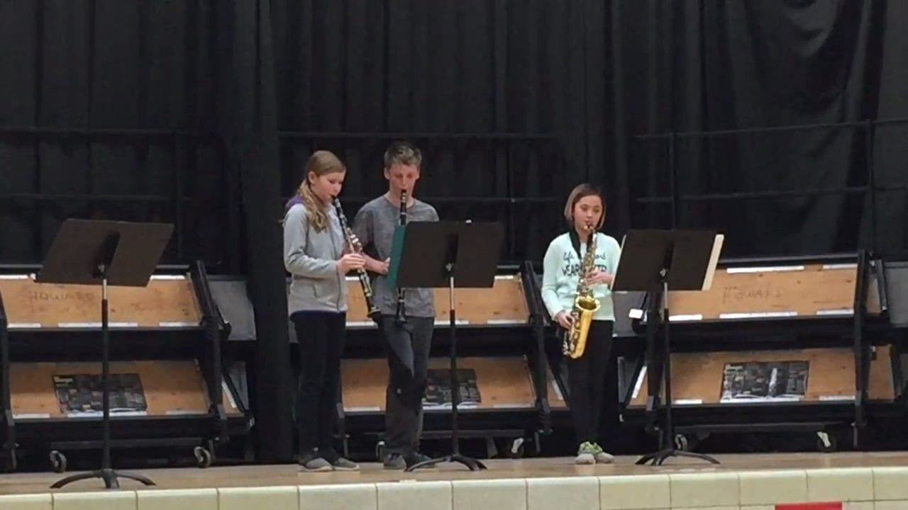 Three very talended band students perform for their school talent show.