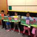 Students holding their artwork that was selected to be displayed at Artspace