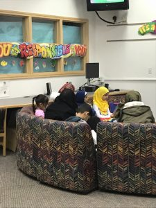 Parents and children reading on media center couch