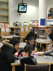 children and parents reading in media center