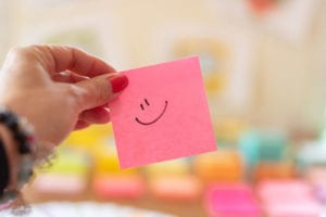 Smily face on pink post it.
