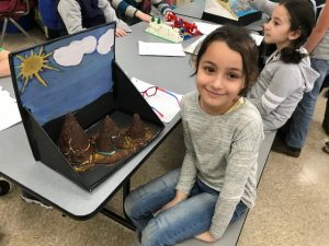 Young girl sitting with her land form project.
