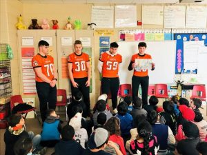 4 high school football players reading to elementary students.