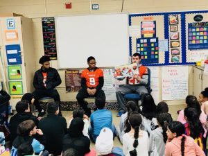 3 high school football players reading to elementary students