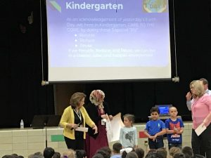 Two teachers and three students presenting to a group.